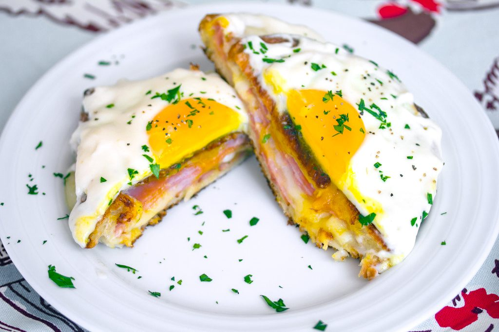 Landscape bird's eye view of a croque madame cut in half on a white plate with parsley sprinkled all around