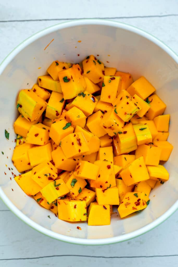 Butternut squash cubes in a bowl with olive oil, sage and red pepper flakes