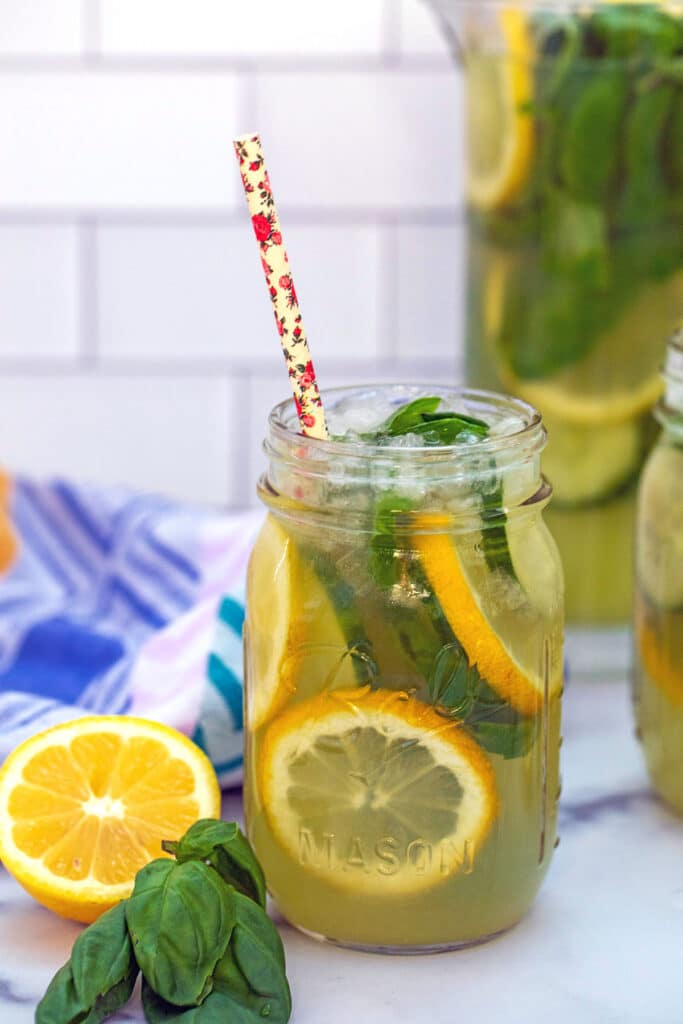 Mason jar of cucumber lemonade with basil and sliced lemons with lemon and basil on the side and pitcher of lemonade in background