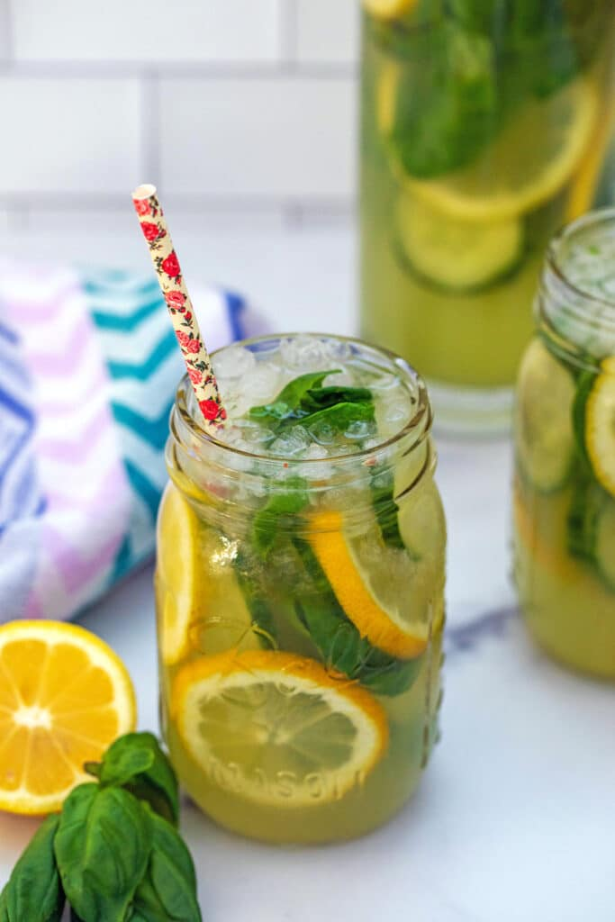 Overhead view of mason jar with cucumber lemonade with basil and lemon slices with straw and more lemonade in background
