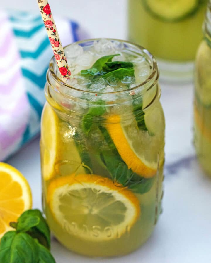 View of a mason jar filled with cucumber lemonade with sliced lemons and basil in it and more glasses of lemonade in background
