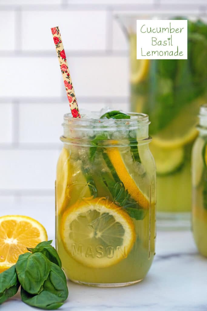 Head-on view of a mason jar of cucumber lemonade with basil, lemon rounds, and straw with pitcher in background and recipe title at top