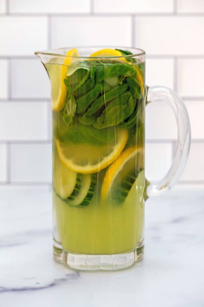 Pitcher of cucumber lemonade with basil, sliced lemons, and sliced cucumbers