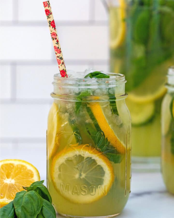 Head-on view of cucumber basil lemonade in a mason jar with sliced lemons, cucumbers, and fresh basil with full pitcher in background