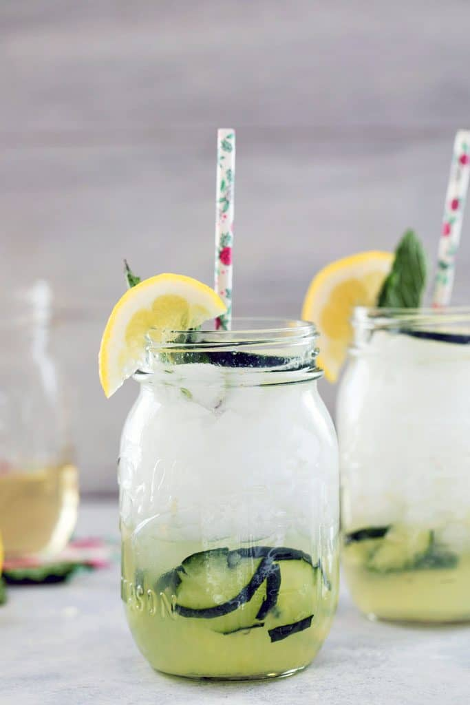 Head-on view of mason jar filled with cucumber collins with cucumbers muddled at the bottom of the glass and topped with a lemon wedge and floral straw and jar of simple syrup in the background