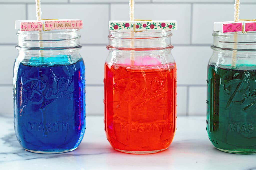 A blue, red, and green jar of sugar solution with sticks hanging out of them for forming rock candy
