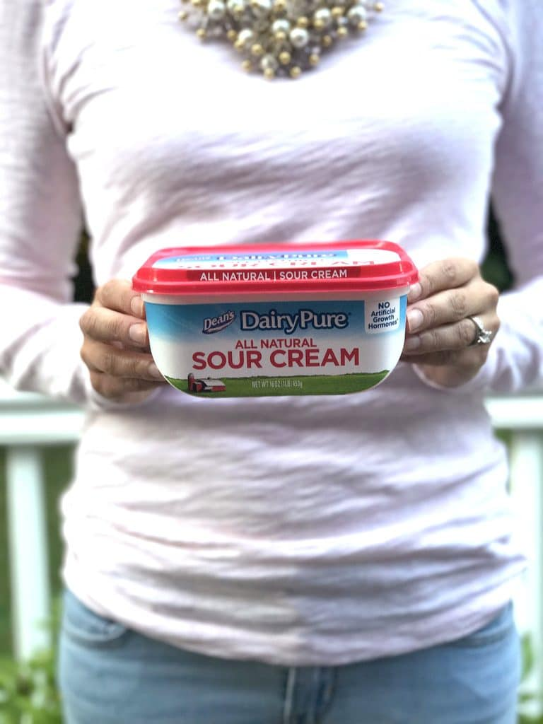 Sues standing and holding a container of DairyPure Sour Cream