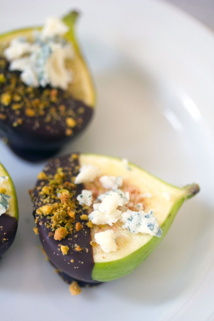 "A close-up of a dark chocolate-dipped fig topped with gorgonzola cheese and crushed pistachios on a white plate with ""Dark Chocolate-Dipped Figs with Gorgonzola"" text on top"