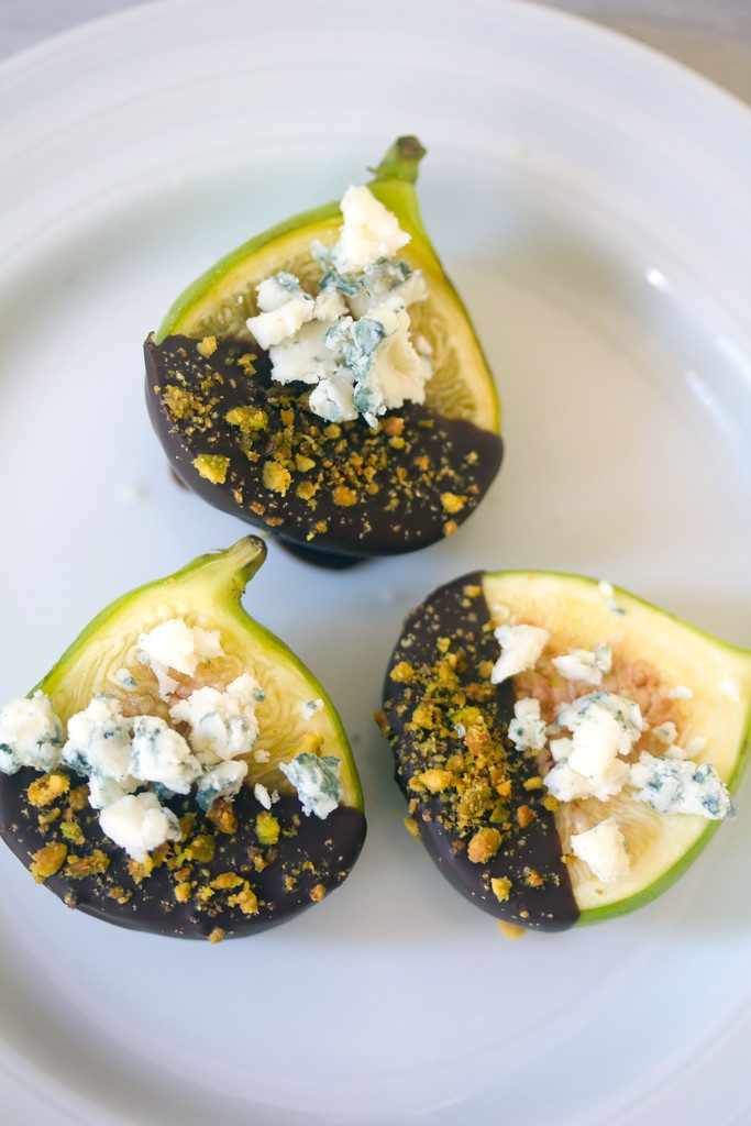 Bird's eye vier of three chocolate dipped figs topped with gorgonzola cheese and crushed pistachios on a white plate
