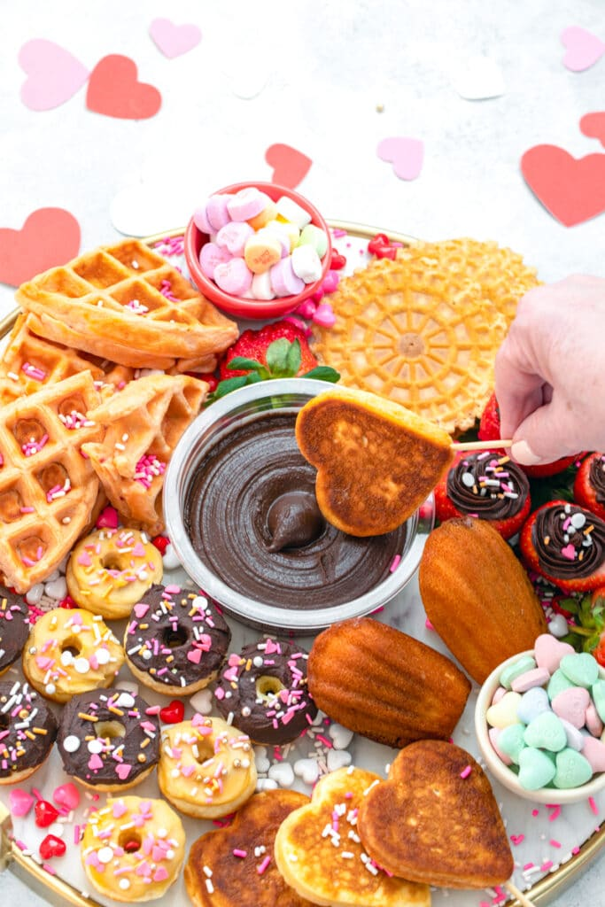 Head-on view of heart-shaped pancake being dipped into chocolate hummus surrounded by other goodies on dessert hummus brunch board