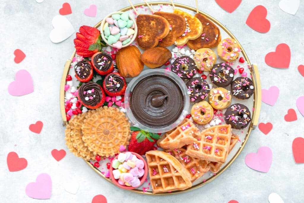 Overhead landscape view of a dessert hummus brunch board featuring dark chocolate hummus surrounded by mini donuts and waffles, heart-shaped pancakes, hummus filled strawberries, pizzells, madeleines, and Valentine's Day candy surrounded by pink, red, and white hearts