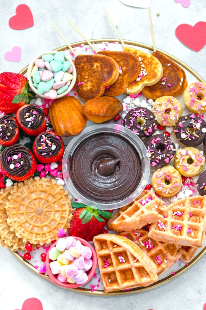 overhead view of a dessert hummus brunch board featuring dark chocolate hummus surrounded by mini donuts and waffles, heart-shaped pancakes, hummus filled strawberries, pizzells, madeleines, and Valentine's Day candy