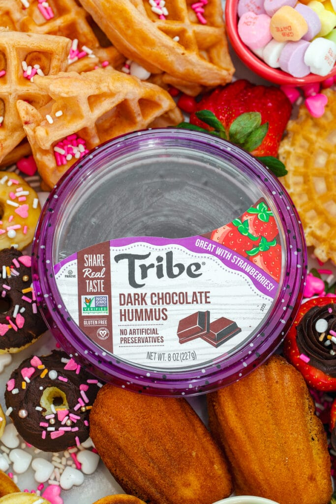 Overhead close-up view of a container of Tribe dark chocolate hummus in the center of a dessert hummus brunch board