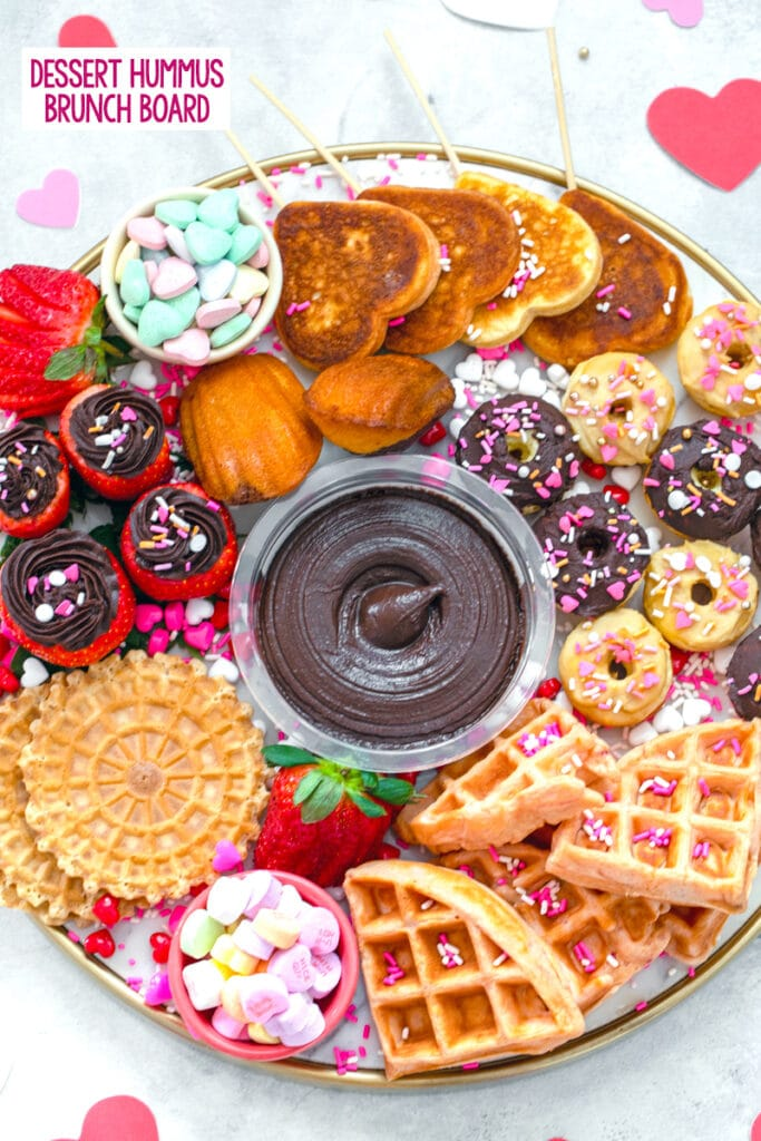 "overhead view of a dessert hummus brunch board featuring dark chocolate hummus surrounded by mini donuts and waffles, heart-shaped pancakes, hummus filled strawberries, pizzells, madeleines, and Valentine's Day candy with ""dessert hummus brunch board"" text at top"