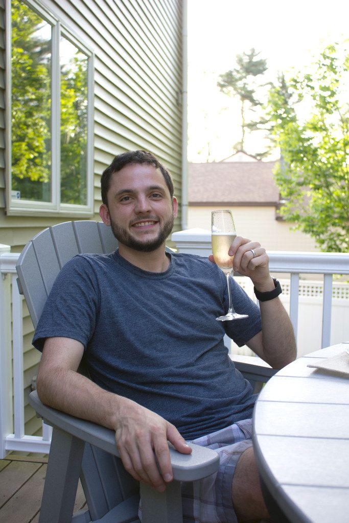 Chris sitting outside holding a glass of champagne