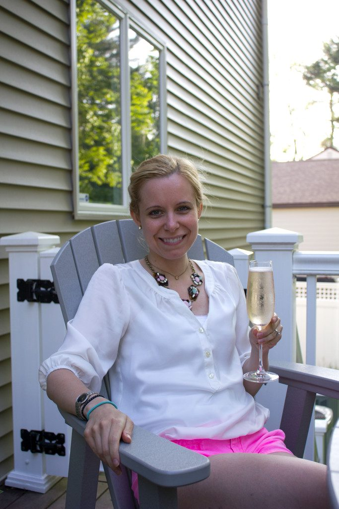 Sues sitting outside holding a glass of champagne