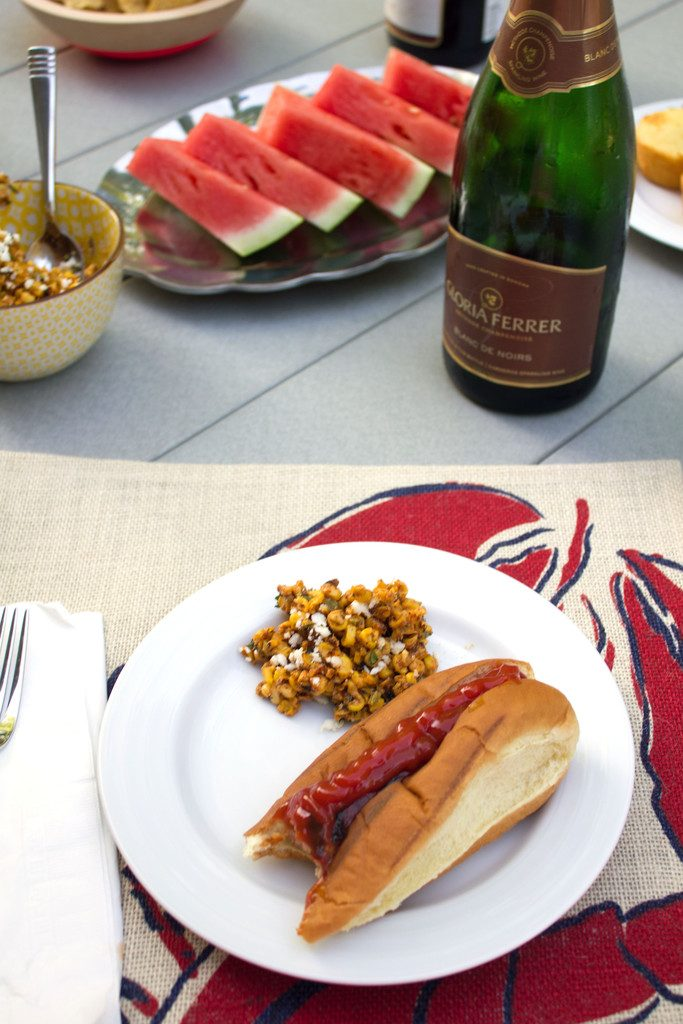 Sausage in bun with bite taken out on plate with side of elote salad and watermelon and champagne bottle in background