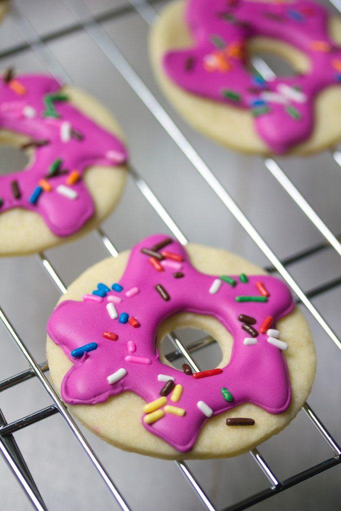 Close-up of a pink frosted doughnut sugar cookie with sprinkles on a baking rack