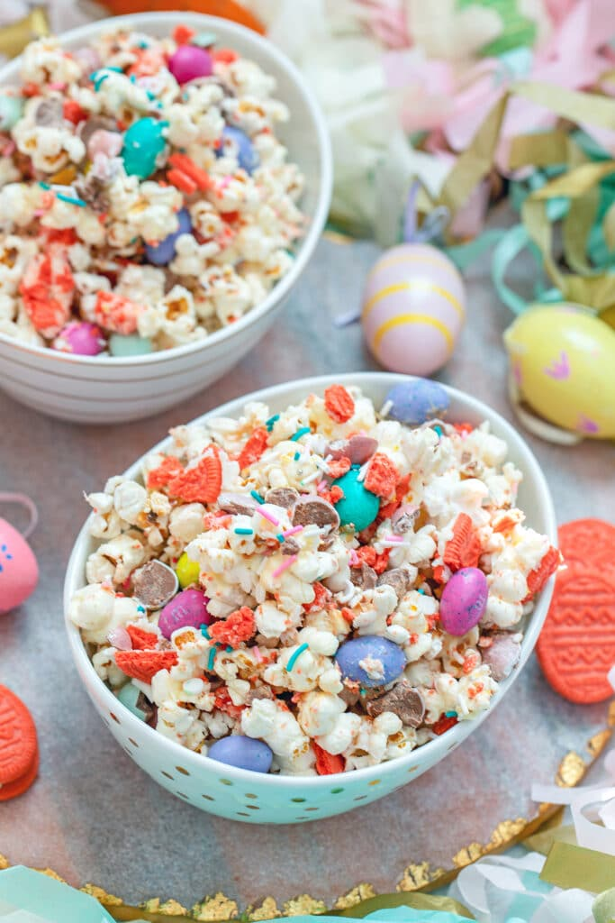 View of a bowl of Easter candy popcorn with M&Ms, sprinkles, and Easter Oreo cookies with second bowl and Easter eggs in background