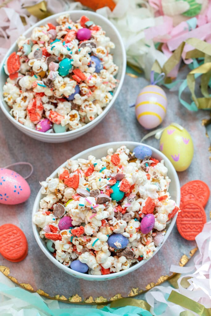 Bird's eye view of two bowls of Easter candy popcorn surrounded by Easer eggs and Oreo cookies