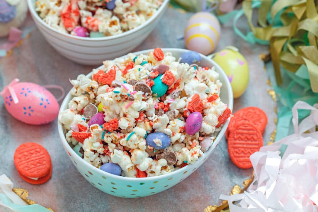 Landscape view of a bowl of Easter candy popcorn with M&Ms and sprinkles surrounded by Easter eggs and Oreo cookies with a second bowl of popcorn in background
