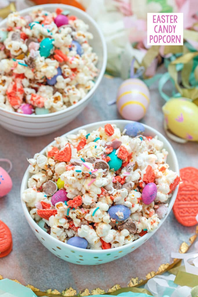 View of a bowl of Easter candy popcorn with M&Ms, sprinkles, and Easter Oreo cookies with second bowl and Easter eggs in background and recipe title at top