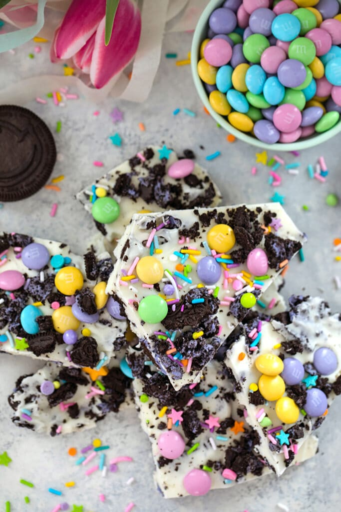 Bird's eye view of stack of white chocolate Easter Oreo bark with spring M&ms, Peeps Oreo cookies, and pastel sprinkles with bowl of M&Ms, pink tulips, cookies, and sprinkles in the background