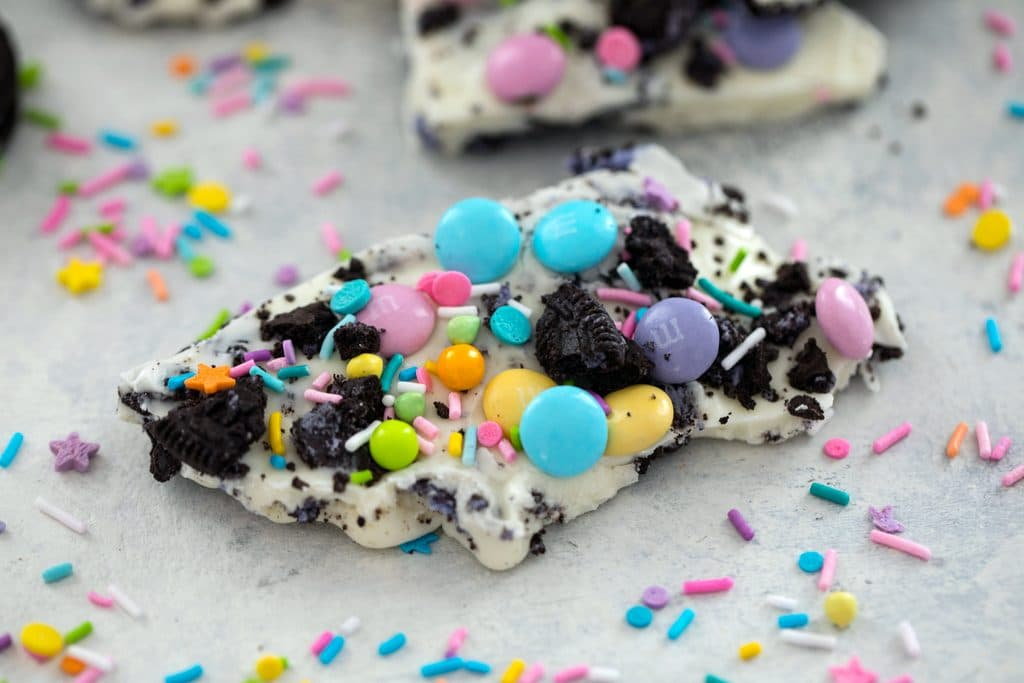 Landscape view of a piece of white chocolate Easter Oreo bark with spring M&Ms, crushed Peeps Oreo cookies, and pastel sprinkles with sprinkles scattered all around