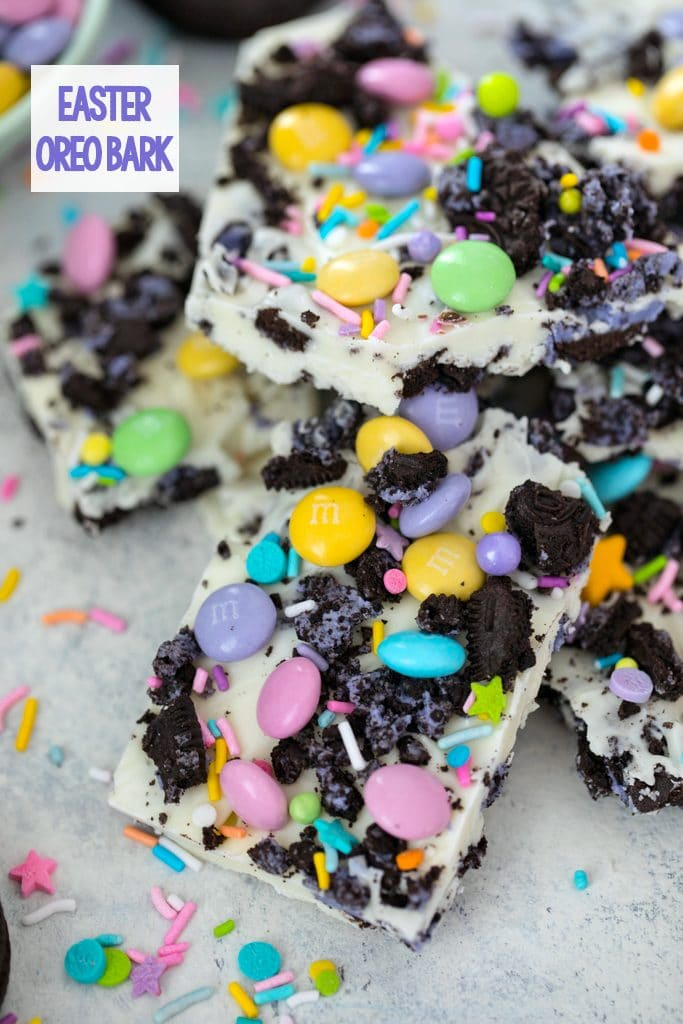 Overhead view of pieces of white chocolate Easter Oreo bark with spring M&Ms, Peeps Oreo cookies, and pastel sprinkles with recipe title at top