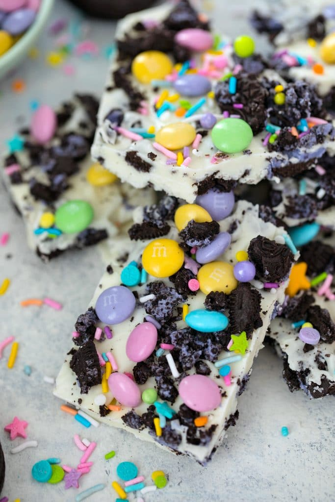 Overhead view of pieces of white chocolate Easter Oreo bark with spring M&Ms, Peeps Oreo cookies, and pastel sprinkles