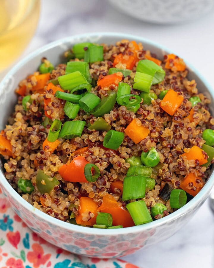 Close-up of quinoa fried rice made with red and white quinoa, bell peppers, carrots, and scallions