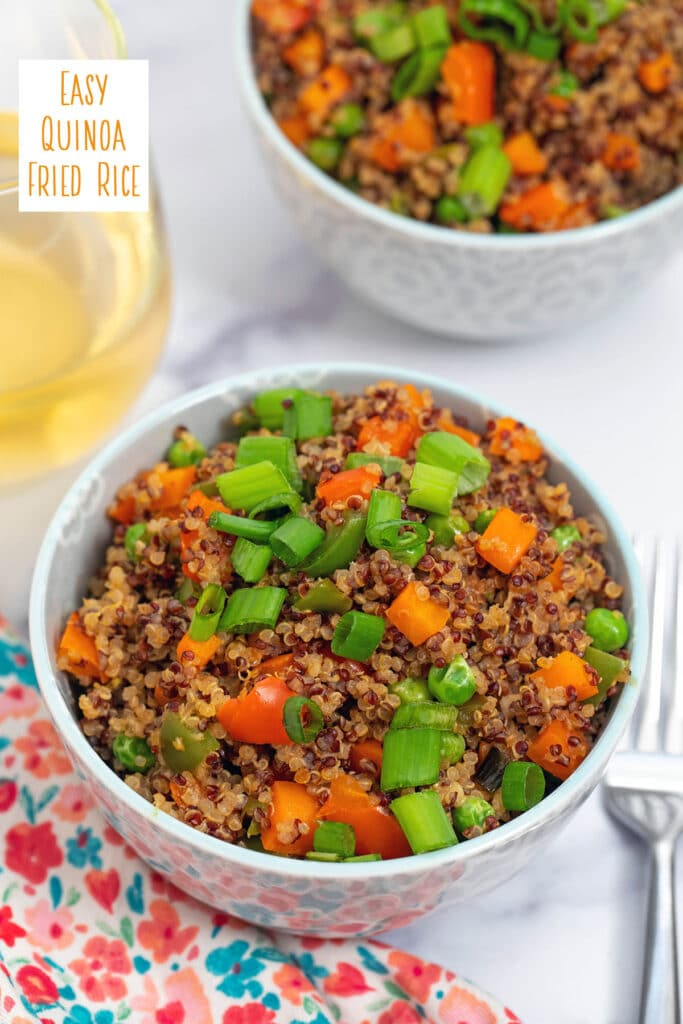 Overhead view of a bowl of quinoa fried rice with red and white quinoa, red and green peppers, carrots, and scallions, with second bowl and glass of white wine in background and recipe title at top