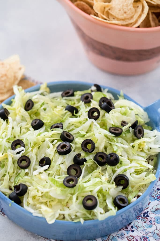 Closeup head-on view of easy taco dip topped with shredded lettuce and sliced olives with bowl of chips in background