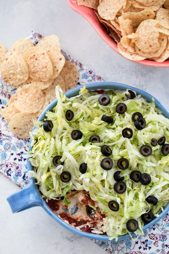 Overhead view of a taco dip with cream cheese, salsa, cheese, lettuce, and olives with chips all around