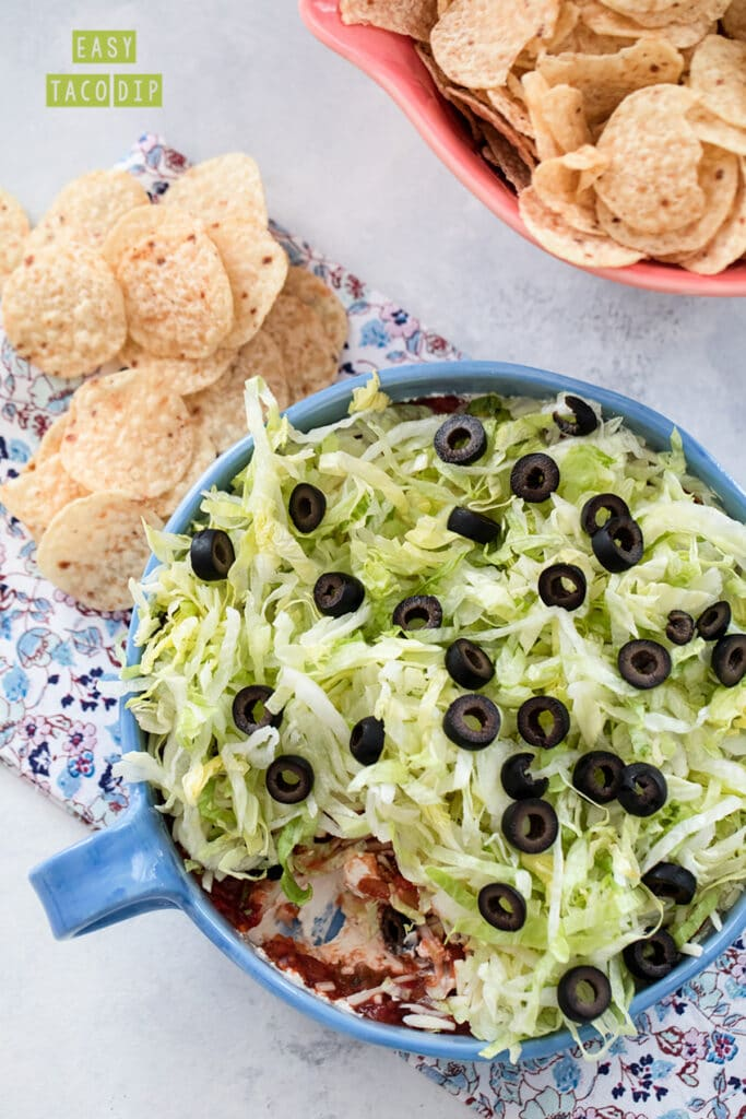 Overhead view of a taco dip with cream cheese, salsa, cheese, lettuce, and olives with chips all around with recipe title at top