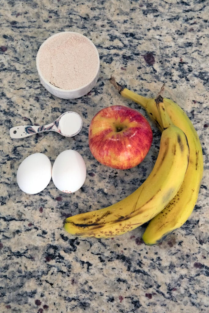 Bananas, apple, eggs, baking powder, and whole wheat flour on counter