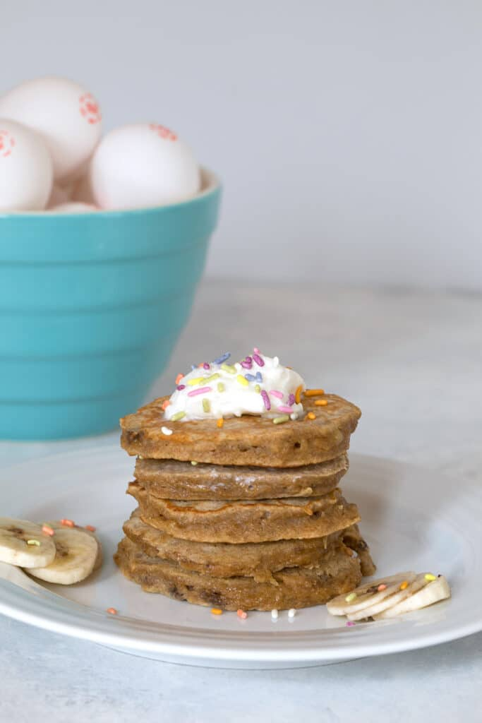 Stack of egg, apple, and banana pancakes for dogs with whipped cream and sprinkles and bowl of eggs in the background