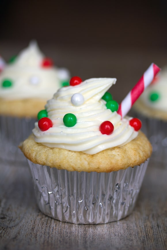 Head-on view of an eggnog cupcake with eggnog frosting and red and green decorations with straw, and more cupcakes in the background