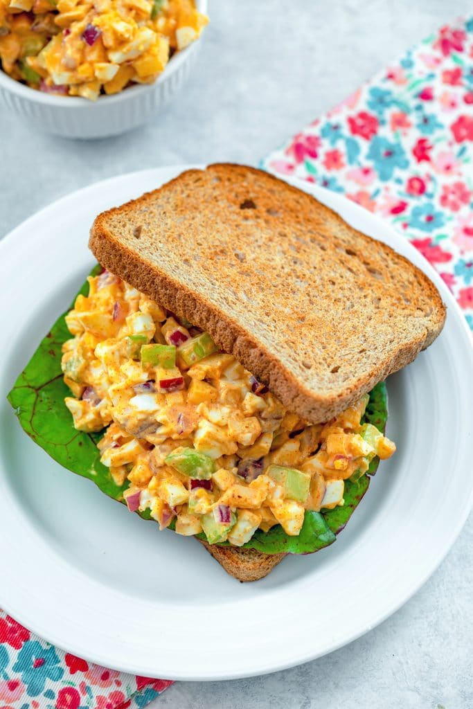Bird's eye view of egg salad with lots of crunch on a sandwich with Swiss chard with bowl of more egg salad in the background