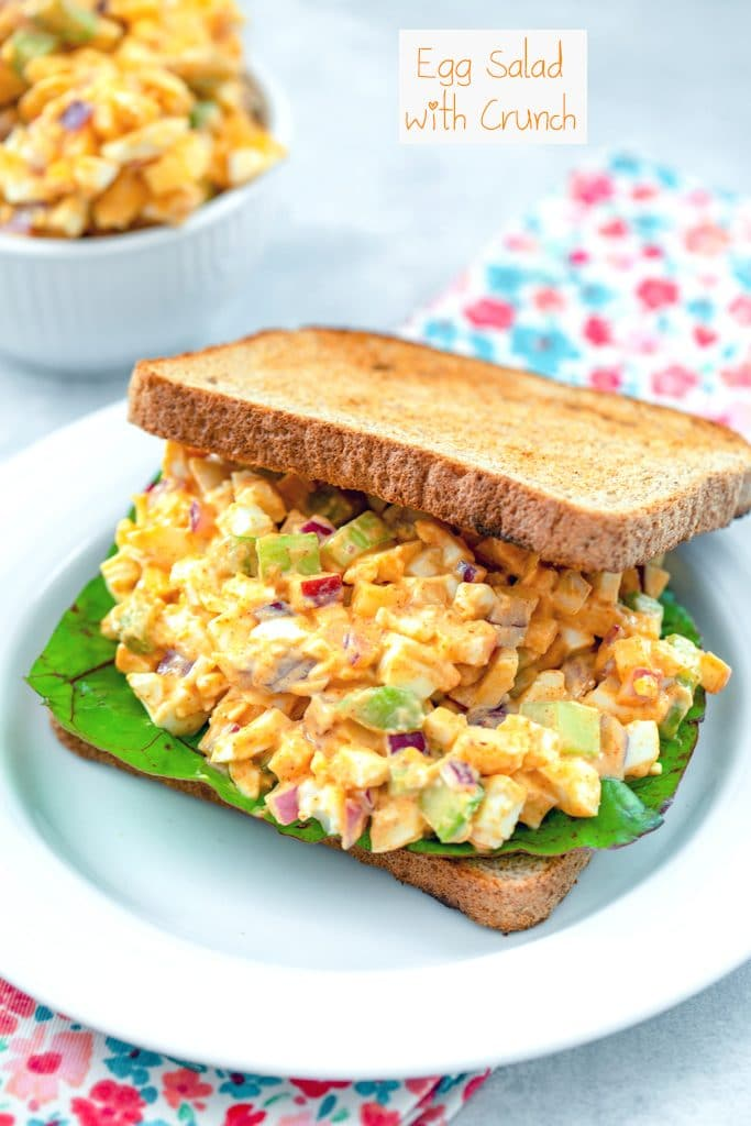 Head-on view of a sandwich with egg salad with lots of crunch with Swiss chard and with a bowl of more crunchy egg salad in the background with recipe title at top