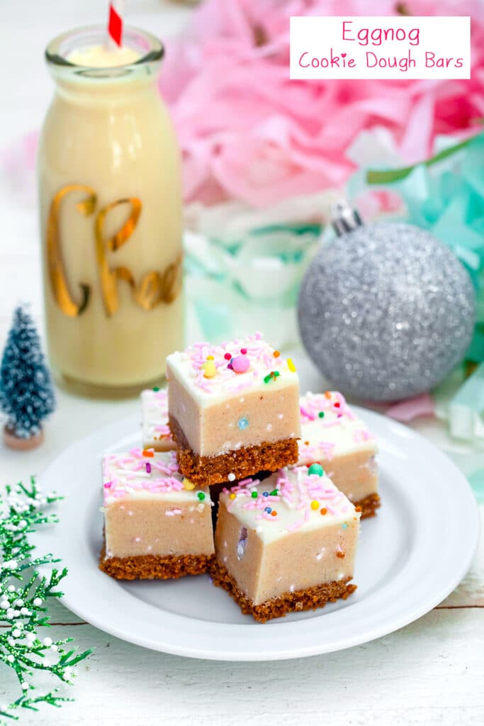 Head-on view of a plate full of eggnog cookie dough bars with eggnog and ornaments in the background with recipe title at top