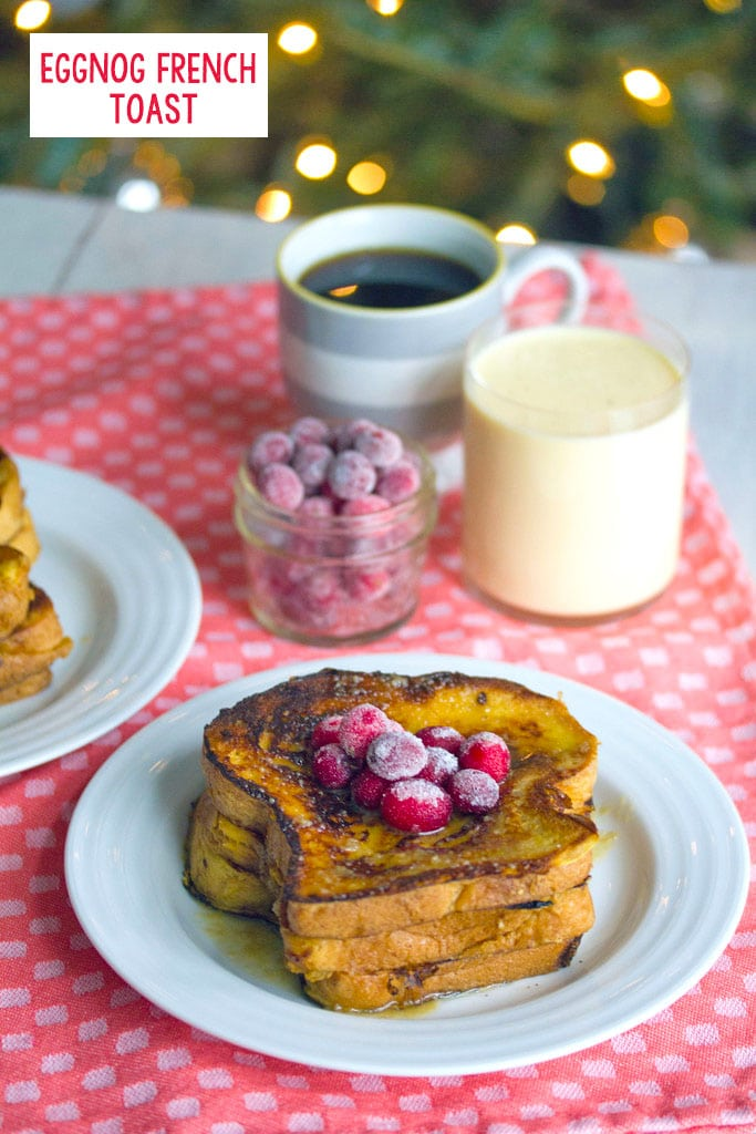 Head-on view of a plate of eggnog french toast topped with sugared cranberries with cup of cranberries, eggnog, and coffee in the background and recipe title at top