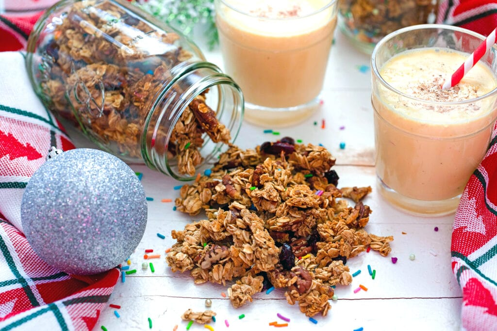 Landscape head-on view of eggnog granola spilling out of mason jar with two glasses of eggnog and silver ornament in background