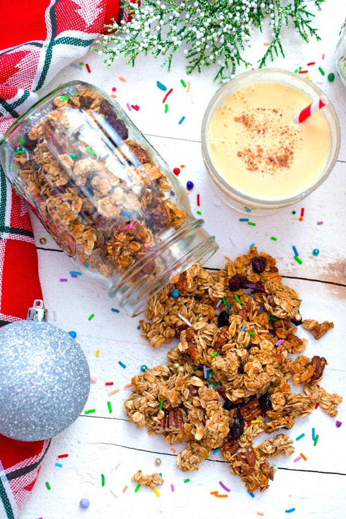 Overhead view of mason jar with eggnog granola spilling out of it with glass of eggnog, silver ornament, and sprinkles in background