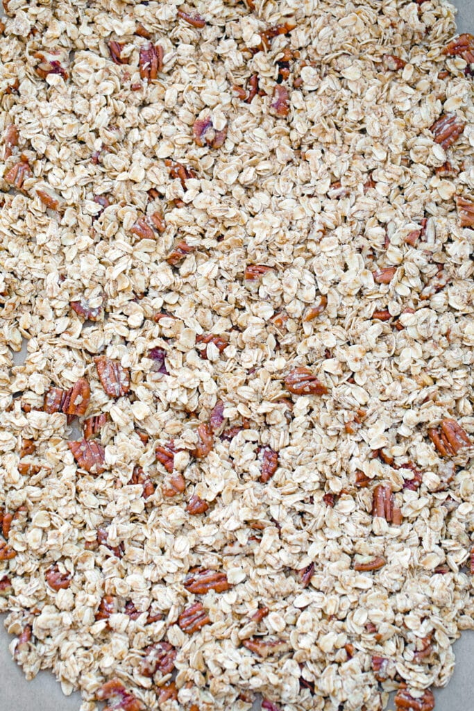 Granola mixture spread out on baking sheet ready to go in oven