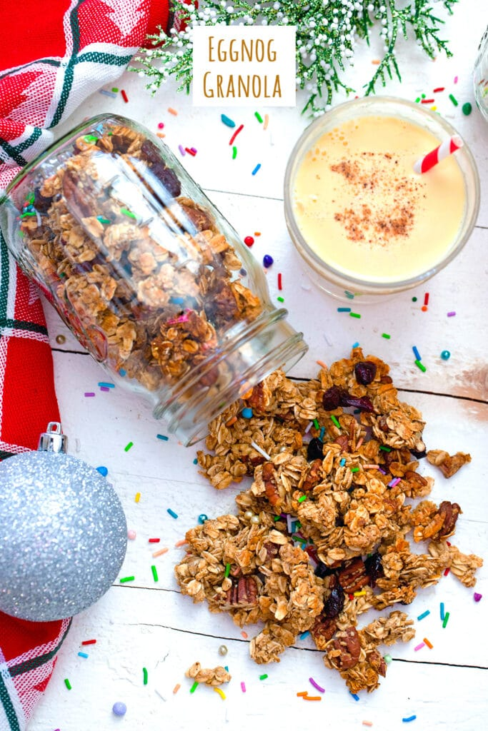 Overhead view of mason jar with eggnog granola spilling out of it with glass of eggnog, silver ornament, and sprinkles in background with recipe title at top