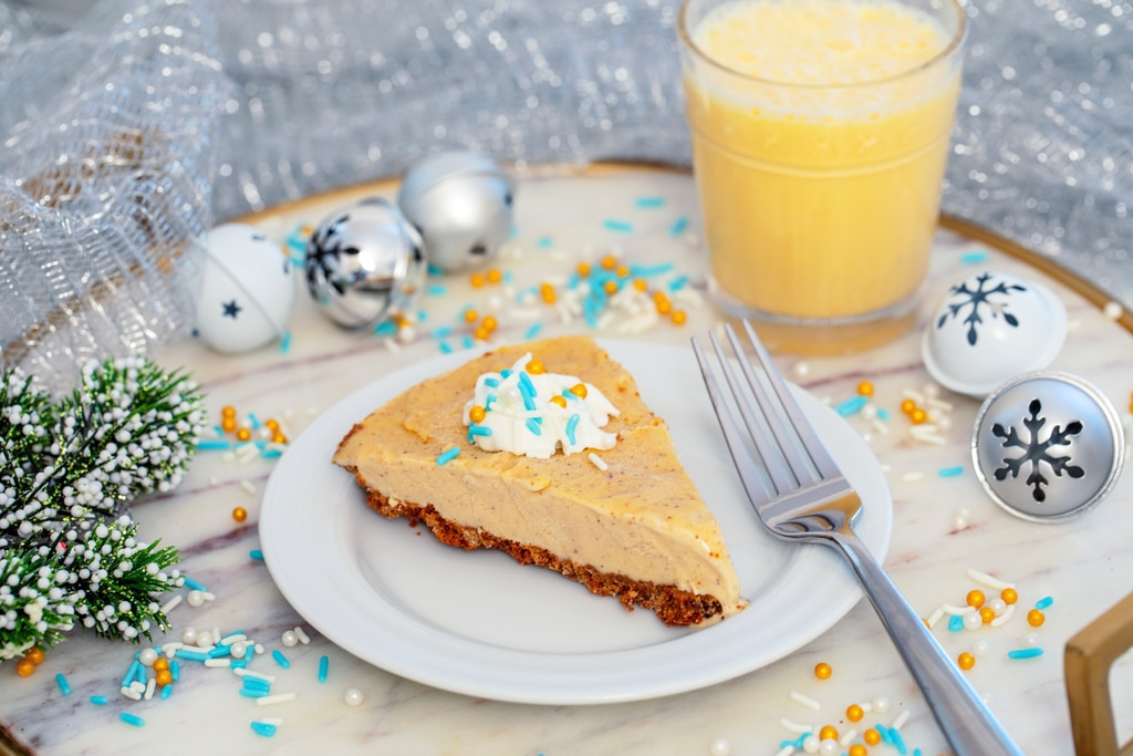 Landscape photo of slice of eggnog ice cream pie on a white plate on a marble tray with fork, sprinkles, Christmas bells, holly, and glass of eggnog in background.