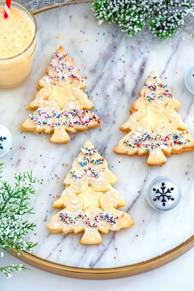 Overhead view of three Christmas tree-shaped eggnog linzer cookies with star cutouts and sprinkles on a marbled surface with glass of eggnog, holly, and Christmas bells in the background