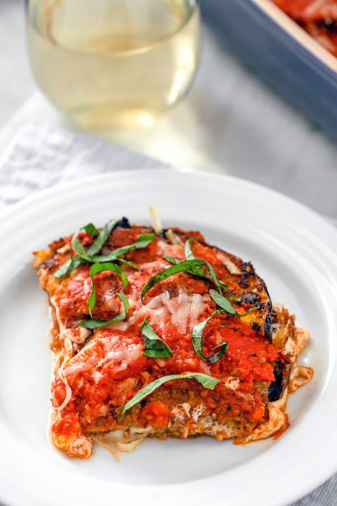 Head-on view of a slice of eggplant parmesan with tomato sauce and basil on a white plate with a glass of white wine in the background