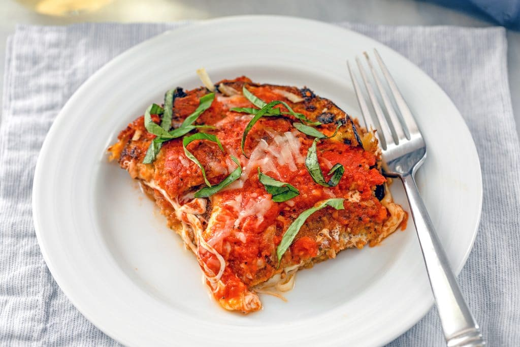 Landscape overhead closeup of slice eggplant parmesan on a white plate with a fork